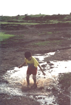 Boy playing in stagnant Water